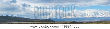 panoramic view of plain at root of mountains at sunny day with cloudy sky on background