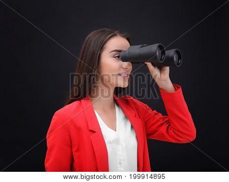 Beautiful young woman with binocular on dark background