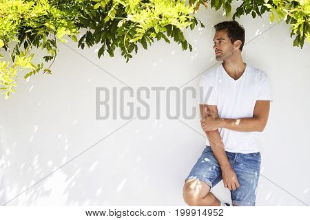 T-shirt guy under plant looking away content