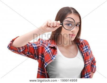 Beautiful young woman with magnifier on white background