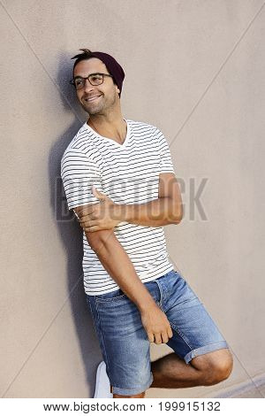 Happy guy in striped t-shirt and hat looking away