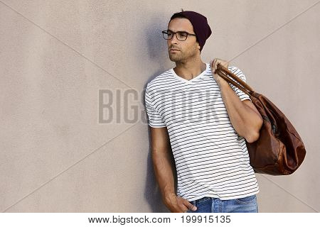 Serious guy in spectacles holding leather bag