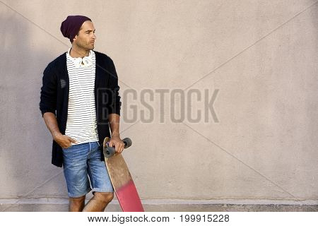 Dude in cool clothes holding skateboard looking away