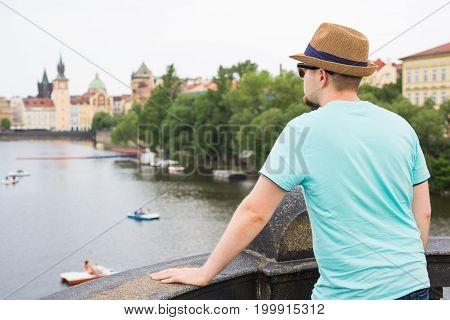 Back view of happy stylish tourist on Charles Bridge, Prague, Czech Republic. Handsome man travelling in Europe