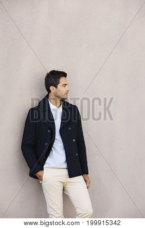 Handsome guy wearing jacket against wall looking away