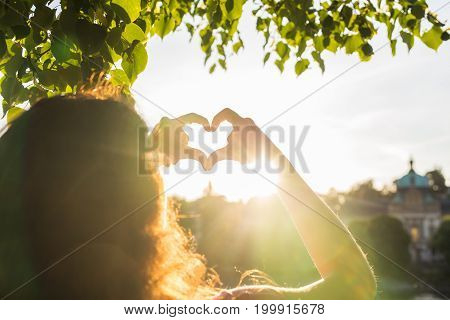 Woman hands showing shape of a heart on sunset, young woman travel alone, love concept