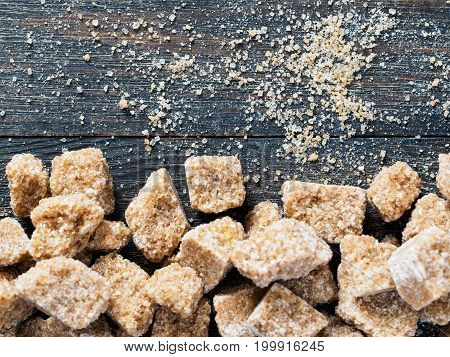 natural raw brown cane sugar cubes and granulated brown sugar on brown wooden background. Top view of brown sugar with copyspace