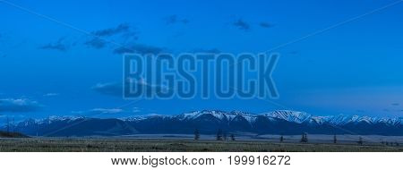panoramic view of plain at root of mountains at summer night