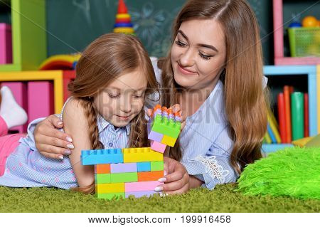 little girl playing with mother at home