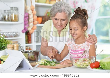 grandmother and granddaughter preparing dinner on table with tablet