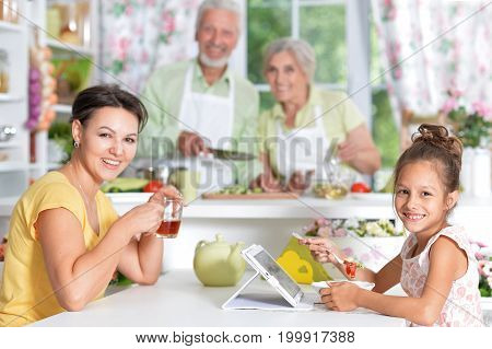Mother and daughter having breakfast together while senior couple cooking on background