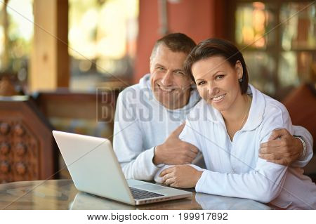 Beautiful young spouse sitting at table with laptop