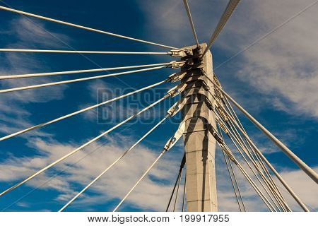 Cable stayed bridge against blue sky, closeup. Upward view