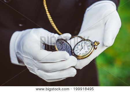 Golden pocket watch in hand in white gloves