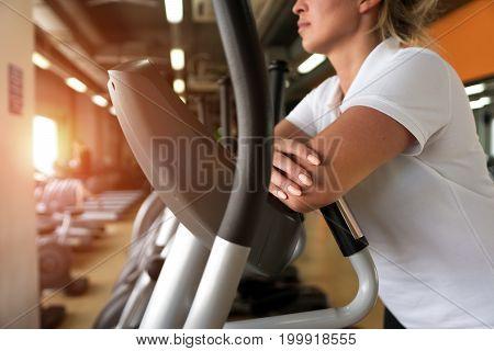 Closeup of female exercising on elliptical machine. Gym equipment