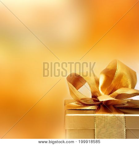 Golden gift with a loop in front of a abstract luminous christmas background