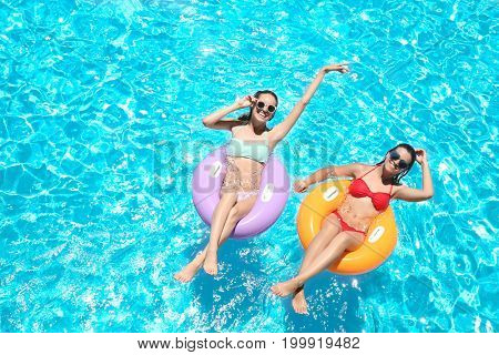 Beautiful young women with inflatable rings in blue swimming pool