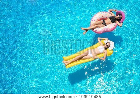 Beautiful young women with inflatable donut and mattress in blue swimming pool