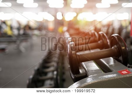 Rows of different dumbbell weights in modern fitness center. Gym equipment background. Shallow depth of field.