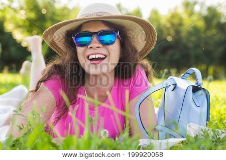 portrait of beautiful young woman with hat and sunglasses lying in park on picnic