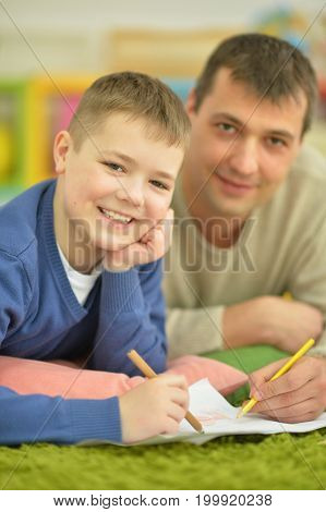 father and son lying on floor and doing homework together