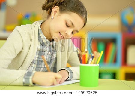 Little schoolgirl doing homework at her room