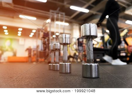 Rows of different dumbbell weights in modern fitness center. Gym equipment. Blurred background of exercising people. Shallow depth of field.
