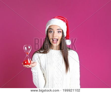 Young woman in Santa hat with sand clock on color background. Christmas countdown concept