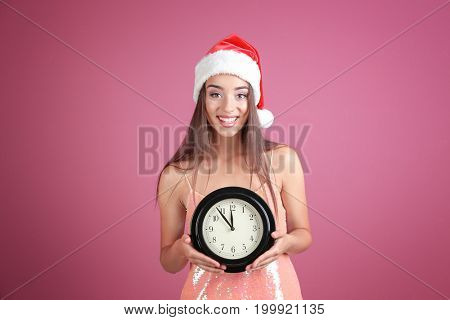 Young woman in Santa hat with clock on color background. Christmas countdown concept