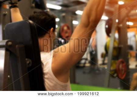 Gym background. Blurred picture of male working out in exercising machine in modern fitness center.