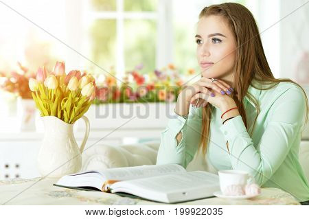Beautiful young woman sitting at table with opened book