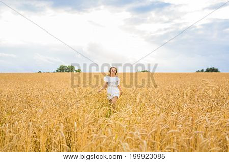 Beautiful woman in a field. happiness, nature, summer, autumn, vacation and people concept - young woman in the field