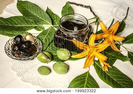 Glass jar with jam of green nuts on the table with walnut leaves and orange lilies