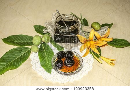 Glass jar with jam from walnuts on walnut leaves and orange lilies on a wooden table