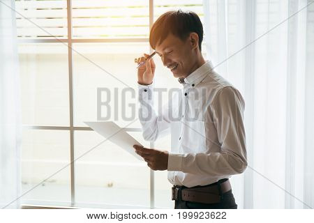Asian male businessman reading business contract documents in private workroom.
