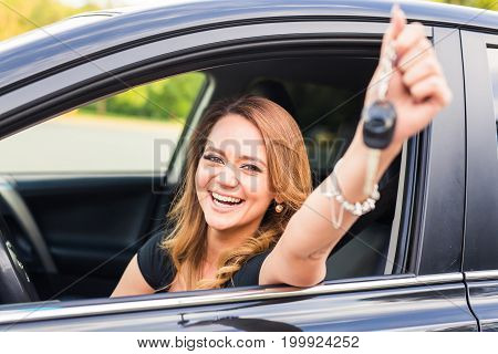 Young happy woman near the car with keys in hand - concept of buying car