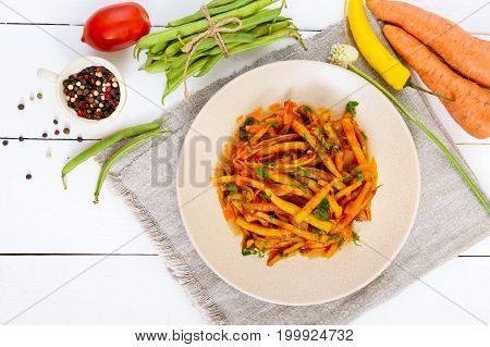 Spicy warm salad of green beans in tomato sauce on a plate on a white wooden background. Vegan dish. Top view.
