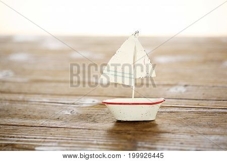 a white sailing boat of the tin plate on wooden table