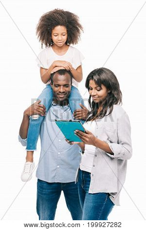 happy african american family with one child using digital tablet together isolated on white