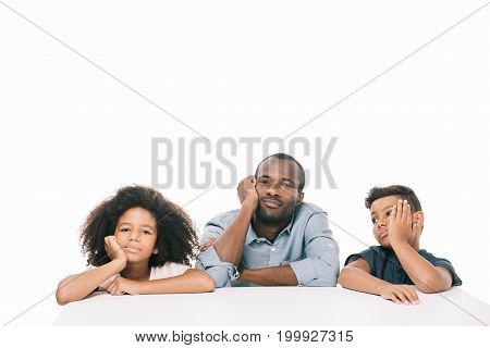 bored african american father with kids holding hands on faces isolated on white
