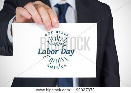 Mature businessman showing card against digital composite image of happy labor day and god bless america text