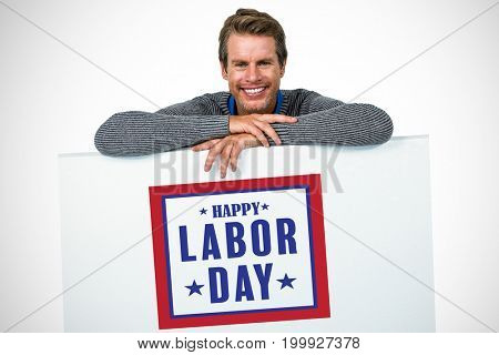 Smiling man on table against white background against composite image of happy labor day poster