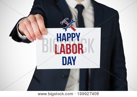 Businessman showing card to camera against digital composite image of happy labor day text with tools