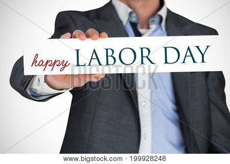 Businessman in grey suit showing card against labor day text