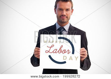 Serious businessman holding a white card against digital composite image of happy labor day text with blue outline