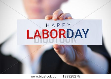 Close up of businesswoman holding blank card against labor day text