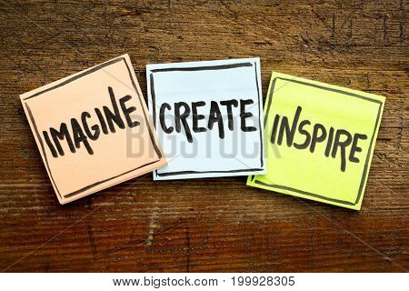 imagine, create, inspire concept - handwriting in black ink on sticky notes against rustic wood