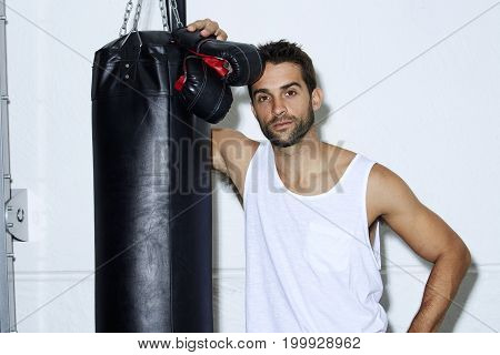 Sporty guy with punch bag in gym portrait