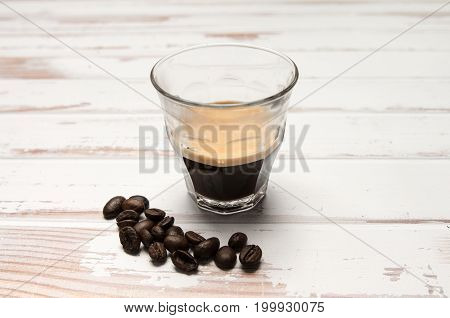 Fresh espresso with crema on a white table with some coffee beans