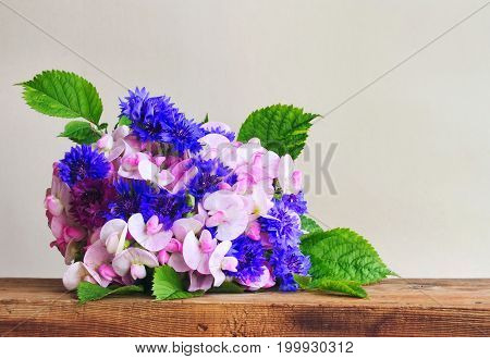 Summer fragrant bunch of cornflowers and sweet peas on wooden table closeup gray wall horizontal